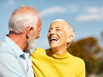 An older woman smiling and looking at her partner after seeing her Assurant Dental dentist in Jacksonville