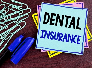 "A pile of paper clips, a blue sharpie, and a stack of post-it notes with the top one reading ""Dental Insurance"""