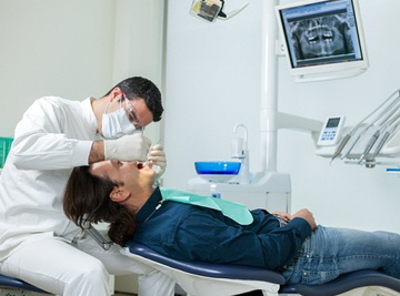 A dentist looking at a patient's mouth