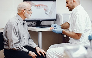 Dentist explaining the cost of dentures in North Jacksonville.