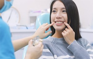 A woman pointing at her smile and listening to a dentist.