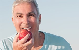 Smiling older man holding a red apple