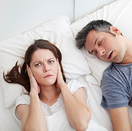 woman sleepless due to snoring husband