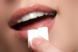 Closeup of woman putting gum in her mouth