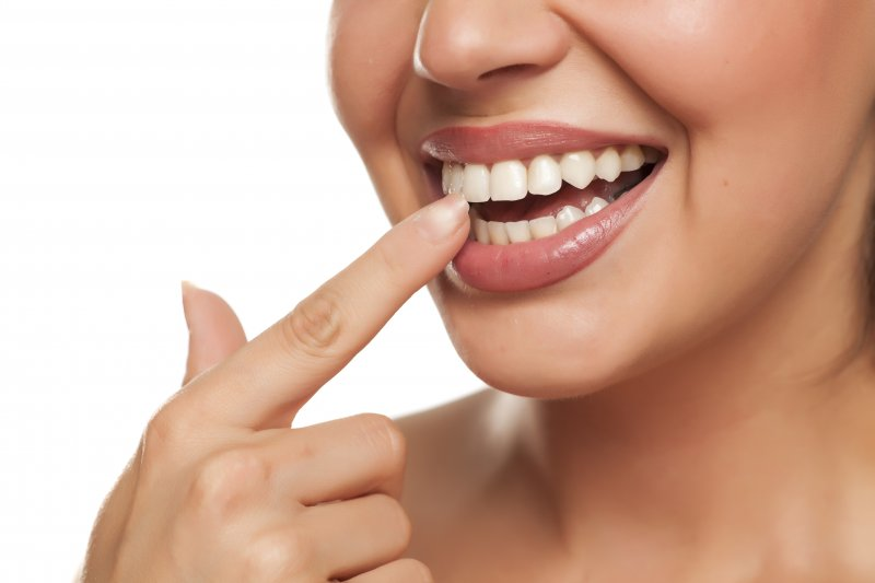 a woman pointing to her teeth