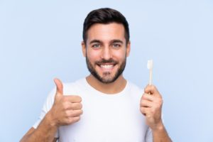 Happy man following dentist's advice for great oral hygiene