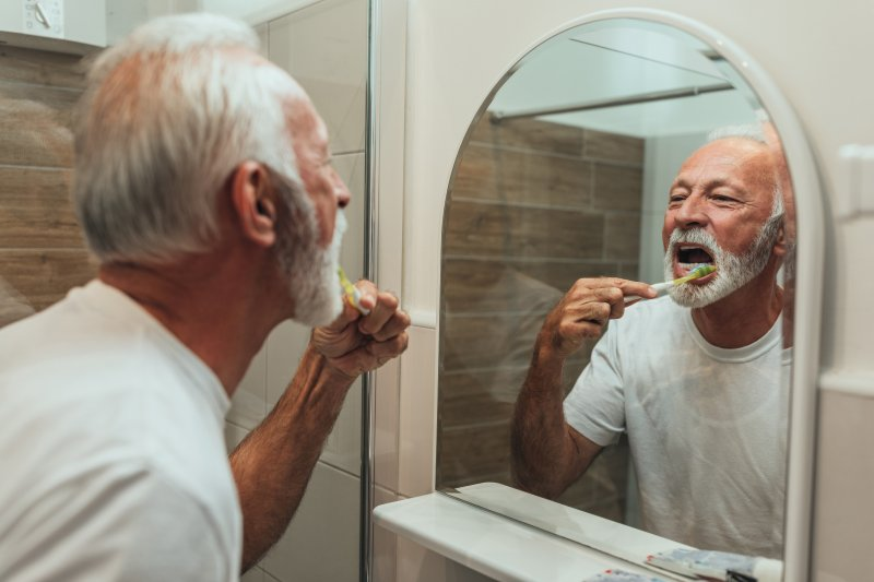 Senior man brushing his teeth in bathroom