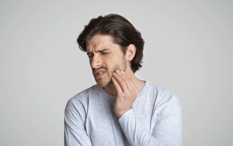 a young man holds his jaw in pain while experiencing a dental emergency